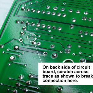 On bottom of circuit board, scratch across the trace as shown to break its continuity.